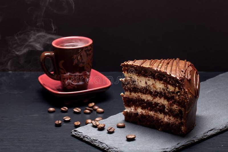 Un morceau de gâteau de chocolat et de tasse de café de plat d'ardoise sur le bl image libre de droits