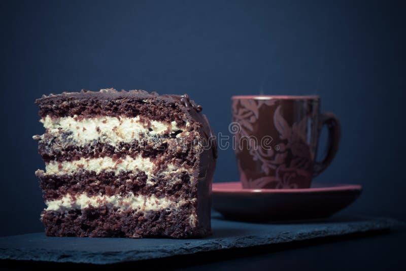 Un morceau de gâteau de chocolat et de tasse de café de plat d'ardoise sur le bl photo libre de droits
