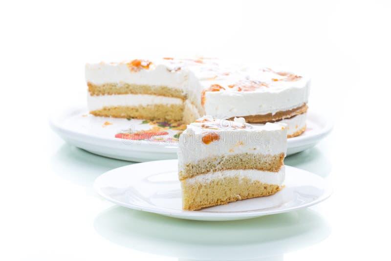 Un morceau de gâteau doux fait maison avec de la crème et les abricots en boîte images stock
