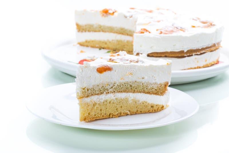 Un morceau de gâteau doux fait maison avec de la crème et les abricots en boîte photos libres de droits