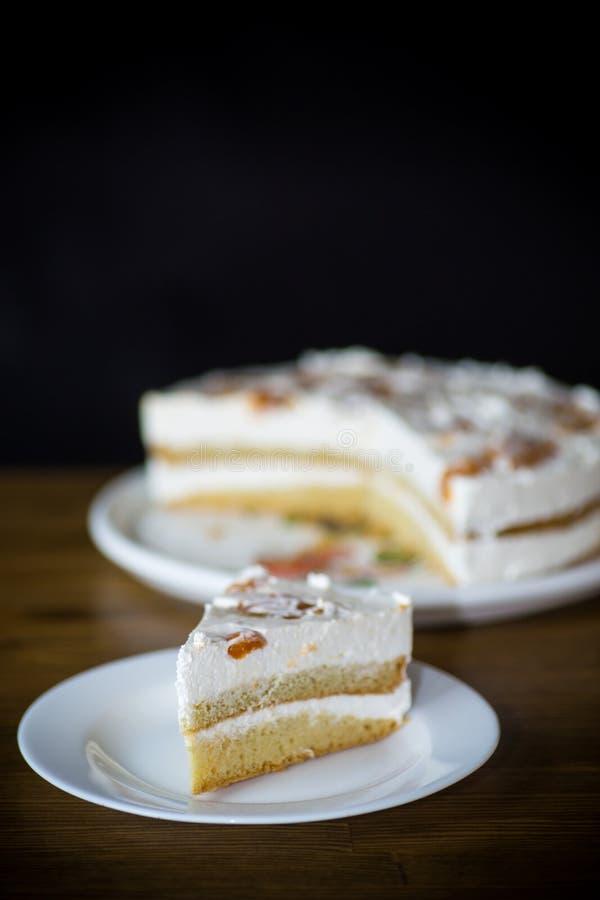 Un morceau de gâteau doux fait maison avec de la crème et les abricots en boîte photo libre de droits
