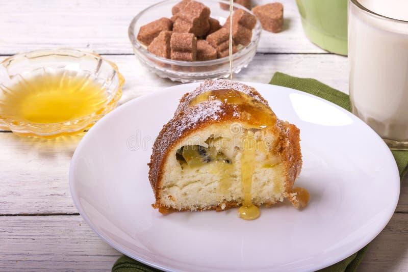 Un morceau de gâteau fait maison de fruit rond doux, sur un plat blanc sur une table en bois, a servi avec une tasse de lait photo libre de droits