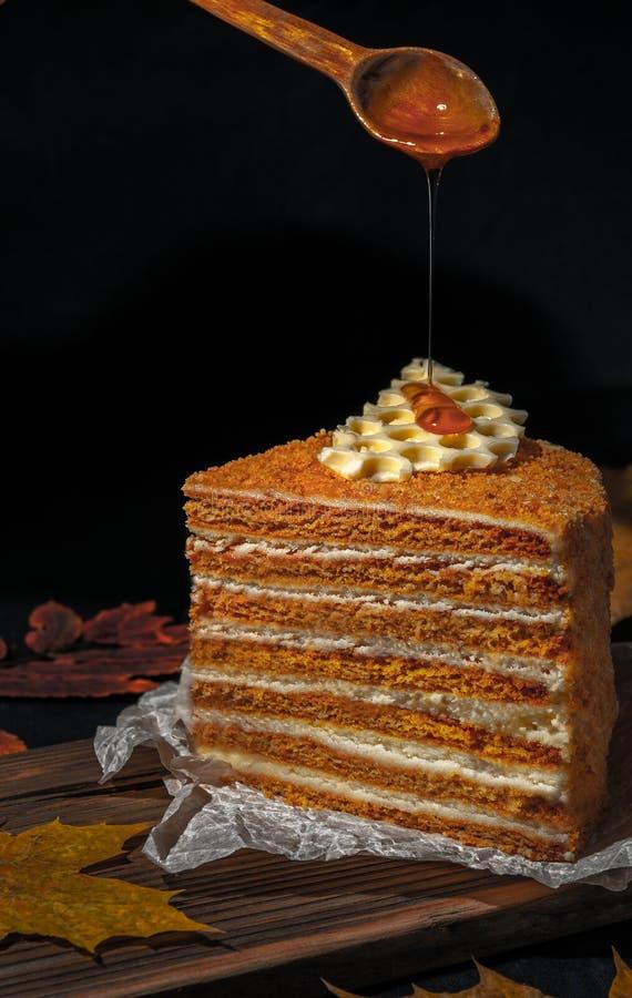 Un morceau de gâteau de miel avec des nids d'abeilles Sur lequel du miel est versé du haut d'une cuillère en bois photo libre de droits