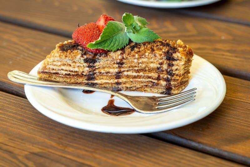 Un morceau de gâteau mousseline de miel décoré des fraises et de la menthe sur une table en bois images libres de droits