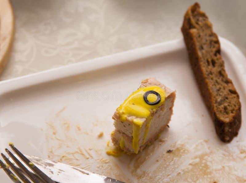 Un morceau de mensonges de croquette de poisson d'un plat avec une tranche de pain brun photos libres de droits