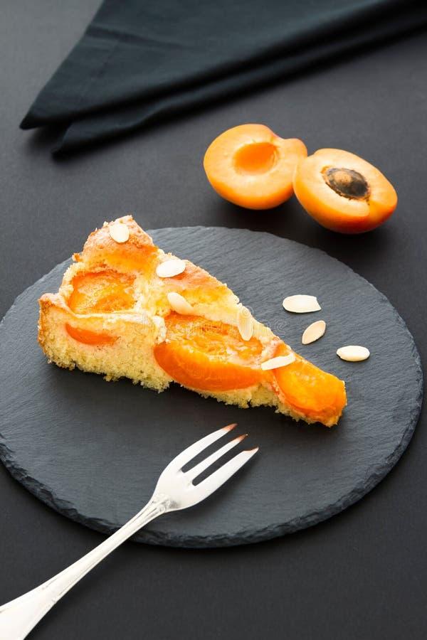 Un morceau de tarte d'abricot avec des rubans d'amande sur une ardoise noire image stock