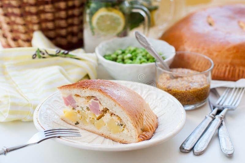 Un morceau de tarte de pomme de terre, de jambon, de crème sure et de fromage photo stock