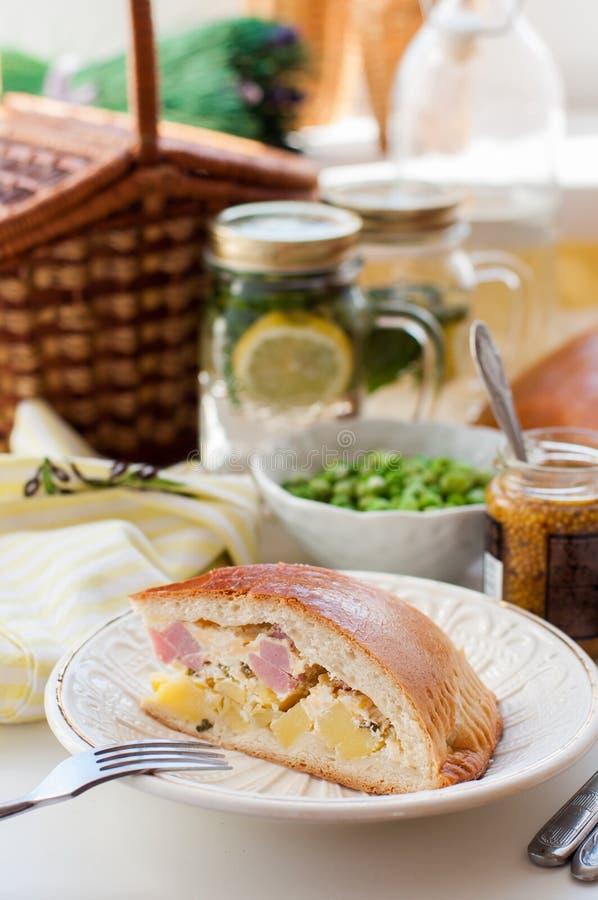 Un morceau de tarte de pomme de terre, de jambon, de crème sure et de fromage images libres de droits