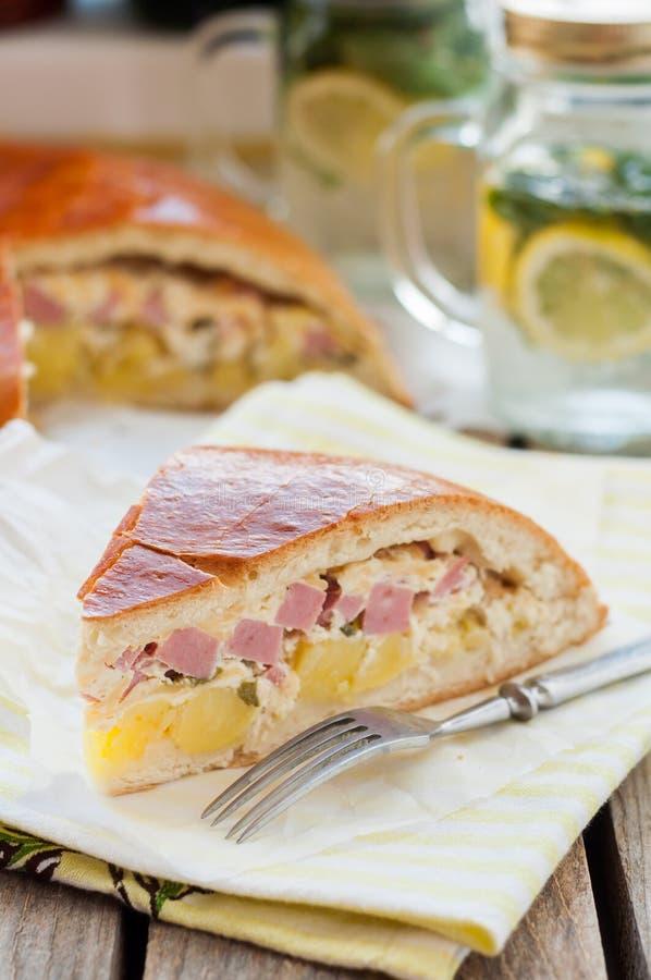 Un morceau de tarte de pomme de terre, de jambon, de crème sure et de fromage photo libre de droits