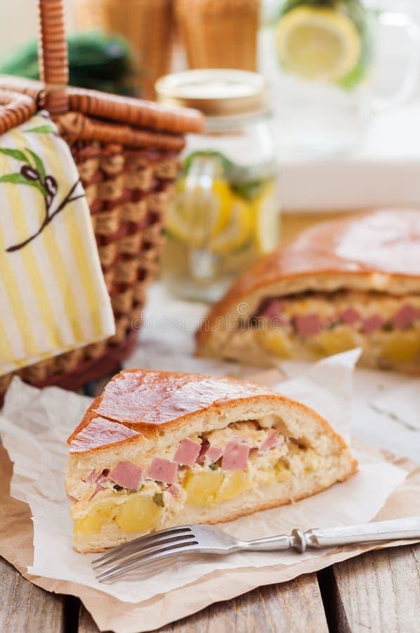 Un morceau de tarte de pomme de terre, de jambon, de crème sure et de fromage photographie stock libre de droits