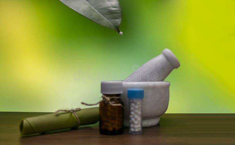 Un mortero, botellas homeopáticas de la medicina de las píldoras con la hoja rodada y un glóbulo homeopático en la extremidad de  imagen de archivo libre de regalías