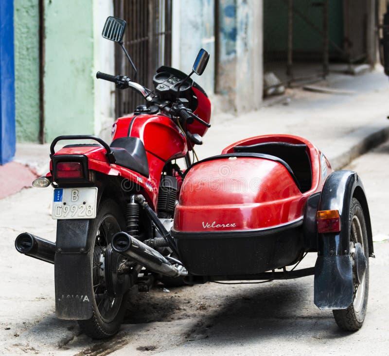 Un mortocylcle rouge de Velorex avec une voiture latérale est garé sur une rue en Havana Cuba photos libres de droits