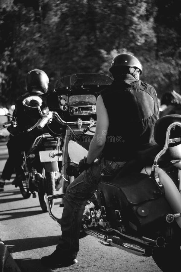 Un motard sur une moto dans la ligne attendant le train image stock