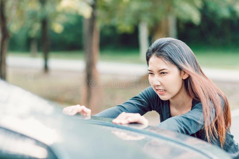 Un moteur d?composent Femme forte poussant une voiture sale Transport, travail d'?quipe, concept photos libres de droits