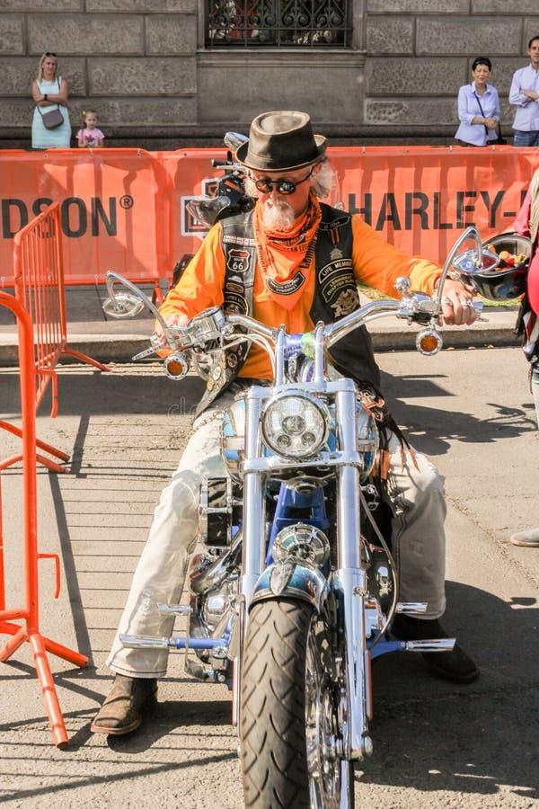 Un motociclista anziano su un motociclo fotografia stock