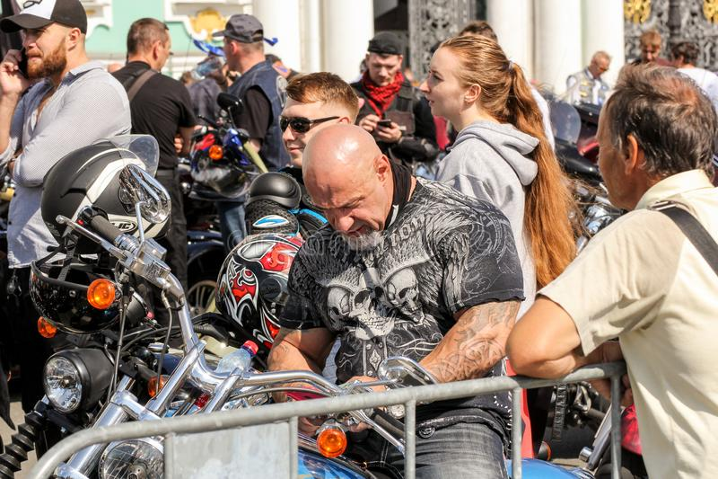 Un motociclista calvo su un motociclo fotografia stock