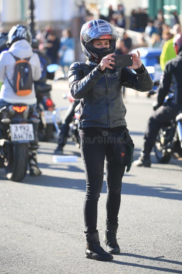 Un motociclista femminile in ingranaggio pieno sta sparando un evento sul suo smartphone immagine stock