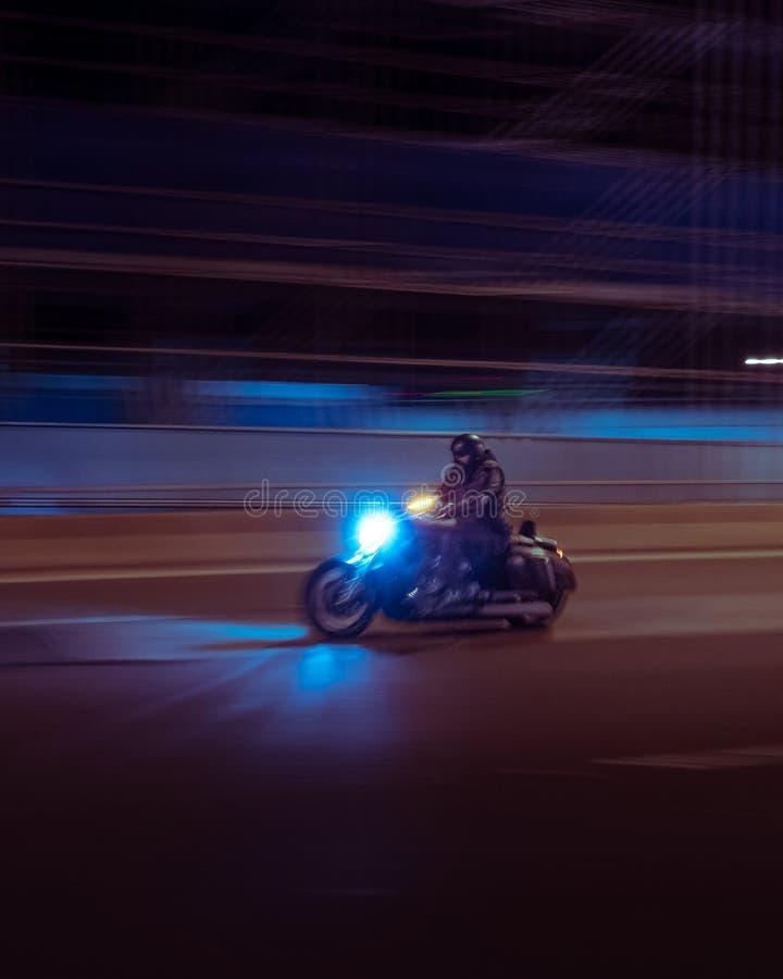 Un motociclista su un motociclo sulla strada che si muove velocemente immagini stock libere da diritti