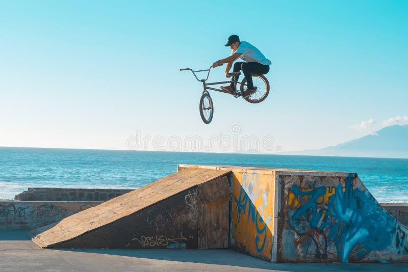 Un motociclista sulla carta da parati tobogan di giorno del jumpbox fotografie stock