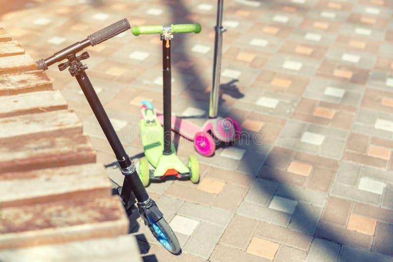 Un motorino di tre bambini parcheggiato ad area del parco il giorno soleggiato luminoso Tipi differenti di supporti del motorino  fotografia stock libera da diritti