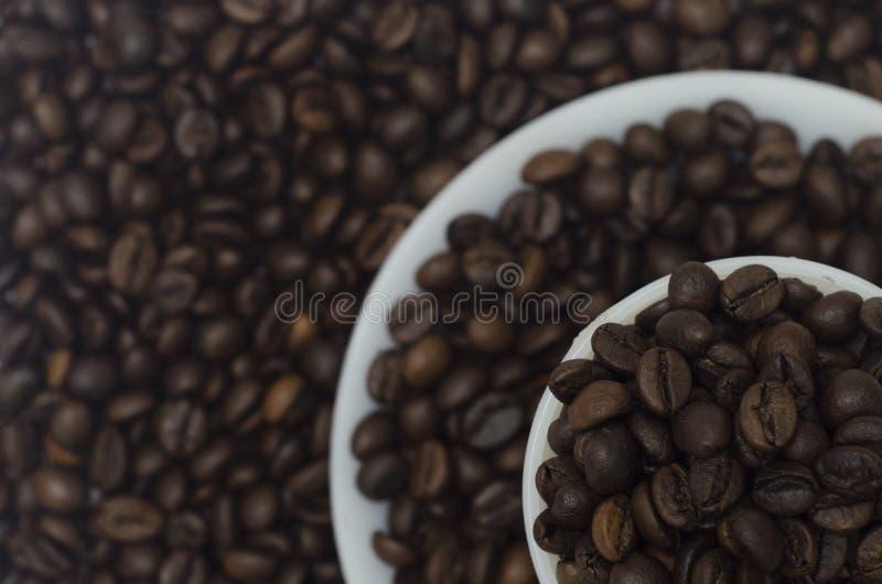 Un mucchio dei chicchi di caffè in tazza e piattino bianchi in 3 strati fotografie stock libere da diritti