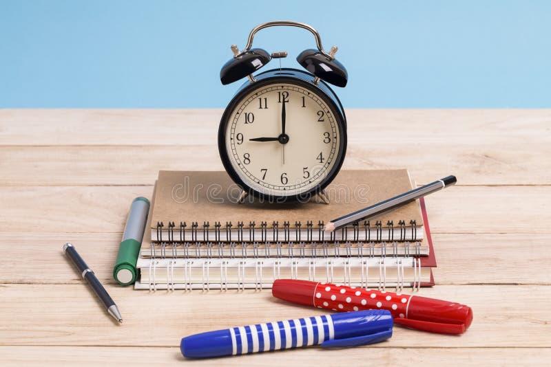 Un mucchio dei libri e con la penna e la sveglia colorate su un woode fotografia stock libera da diritti