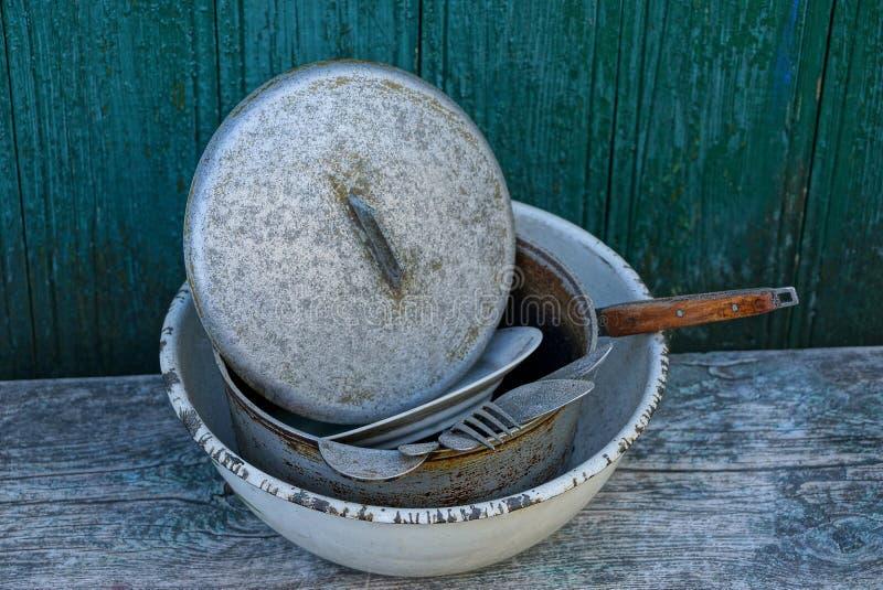 Un mucchio dei piatti sporchi in una ciotola grigia del metallo su una tavola contro una parete verde immagine stock libera da diritti