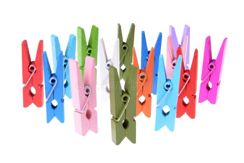 Un mucchio delle clip di legno colorate dei vestiti isolate fotografie stock