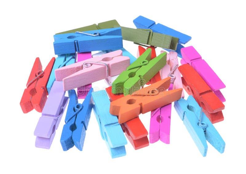 Un mucchio delle clip di legno colorate dei vestiti isolate immagine stock libera da diritti