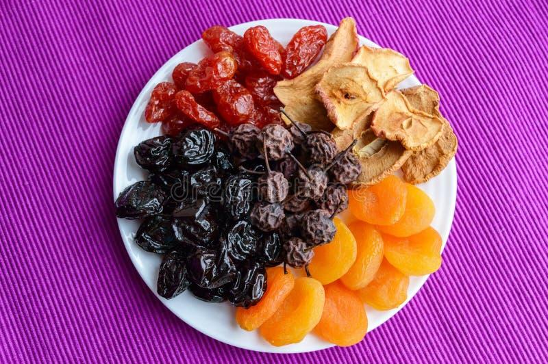 Un mucchio delle mele secche di frutti, prugne, albicocche, pere, mirtilli rossi su un piatto bianco su un fondo porpora Miscela  immagini stock