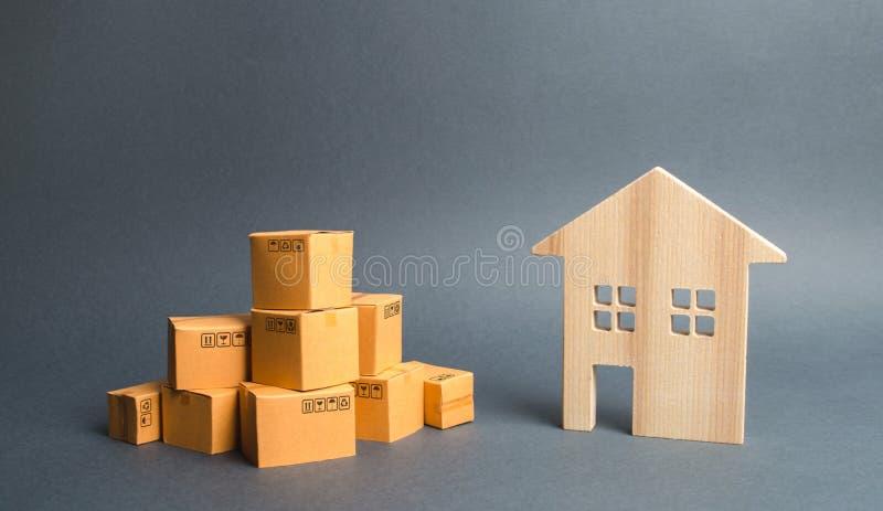 Un mucchio delle scatole di cartone e di una casa residenziale Concetto di muoversi verso un'altra casa o città inizio di una fas immagini stock libere da diritti
