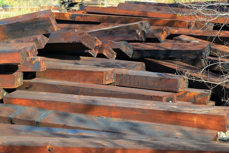 Un mucchio delle traversine ferroviarie di legno marroni all'aperto un giorno soleggiato fotografie stock libere da diritti