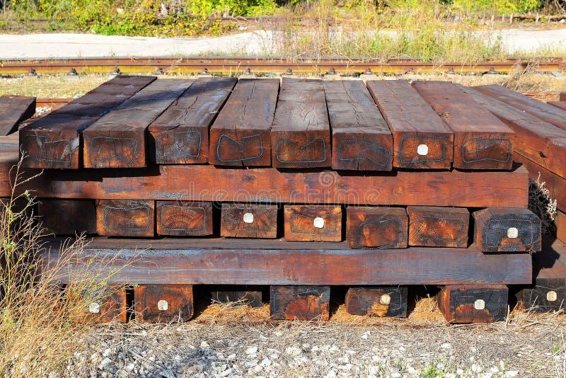 Un mucchio delle traversine ferroviarie di legno marroni all'aperto un giorno soleggiato immagini stock libere da diritti