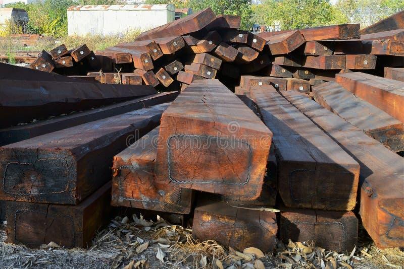 Un mucchio delle traversine ferroviarie di legno marroni all'aperto un giorno soleggiato immagine stock libera da diritti