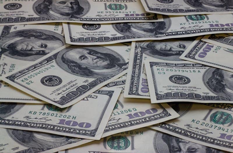 Un mucchio di cento banconote degli Stati Uniti con i ritratti di presidente fotografia stock