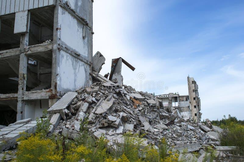 Un mucchio di detriti concreti con il resti di grande costruzione contro il cielo blu Fondo Spazio del testo fotografia stock libera da diritti