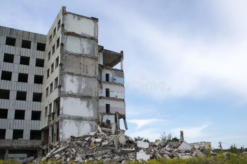 Un mucchio di detriti concreti con il resti di grande costruzione contro il cielo blu Fondo Spazio del testo immagine stock libera da diritti