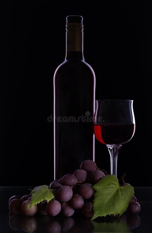 Un mucchio di uva, una bottiglia e un bicchiere pieno di vino rosso fotografie stock