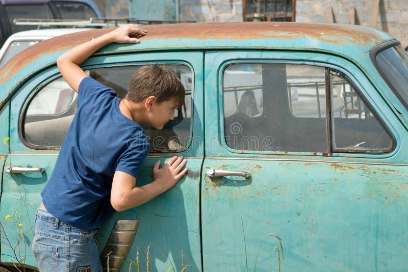 Un muchacho, 11 años, mira hacia fuera la ventana de un coche oxidado en una descarga de coches viejos abandonados en un día de v imagen de archivo libre de regalías