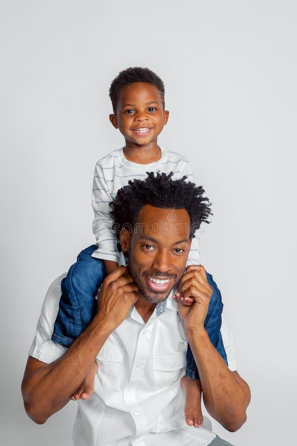 Un muchacho afroamericano joven se sienta encima de los hombros de su papá foto de archivo libre de regalías