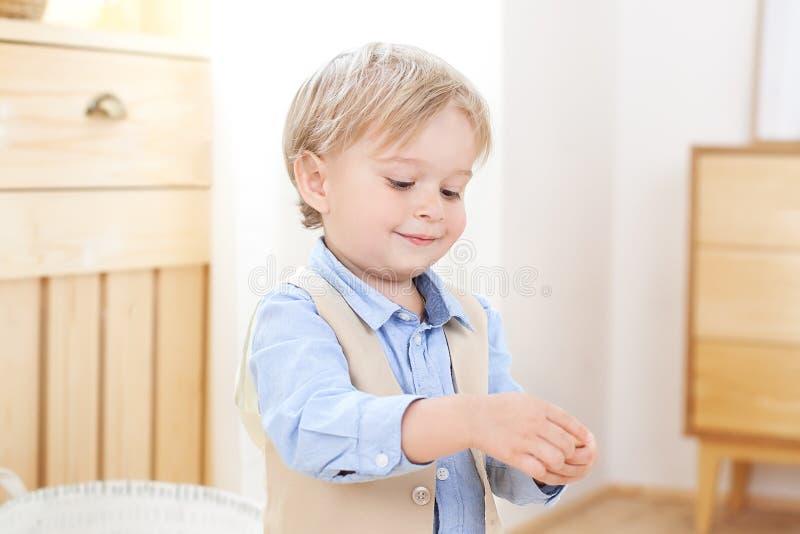 Un muchacho alegre y sonriente lleva a cabo una figura en sus manos Ni?o en guarder?a Retrato del ni?o masculino de moda Posición fotografía de archivo libre de regalías