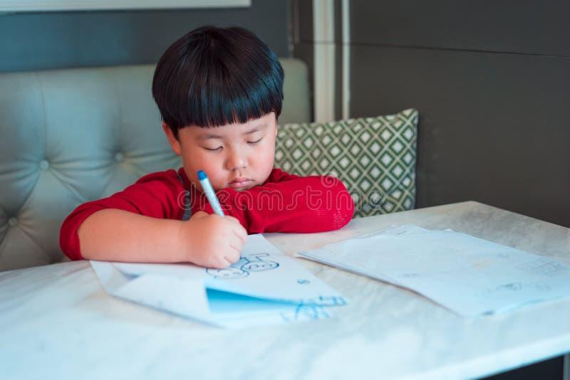Un muchacho asiático está dibujando una imagen imagen de archivo