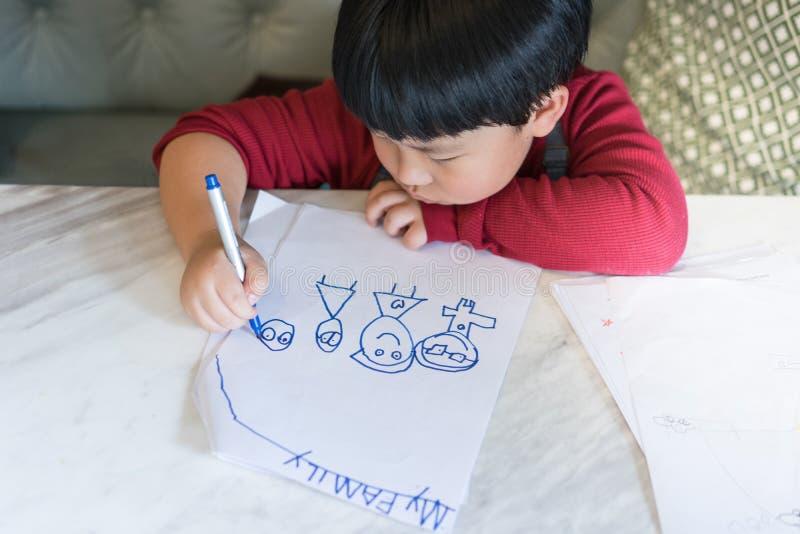 Un muchacho asiático está dibujando una imagen imagen de archivo libre de regalías