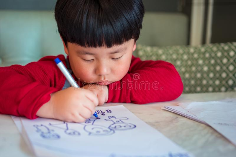 Un muchacho asiático está dibujando una imagen fotos de archivo