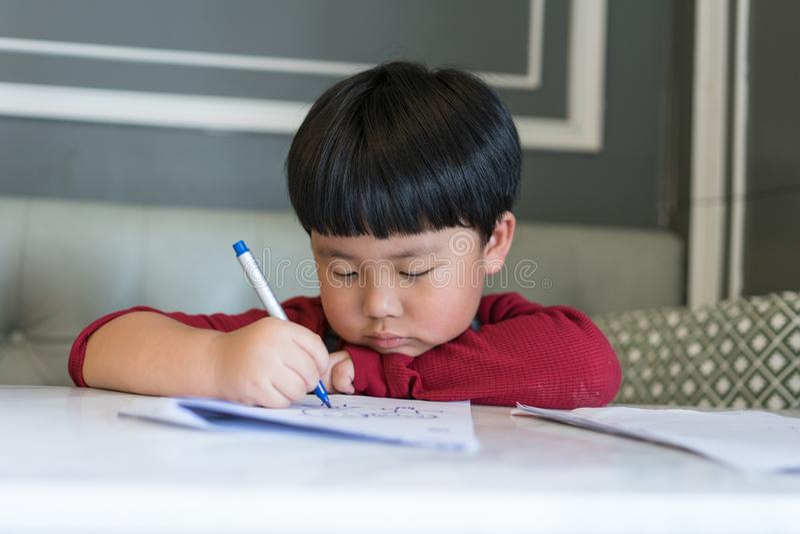 Un muchacho asiático está dibujando una imagen foto de archivo