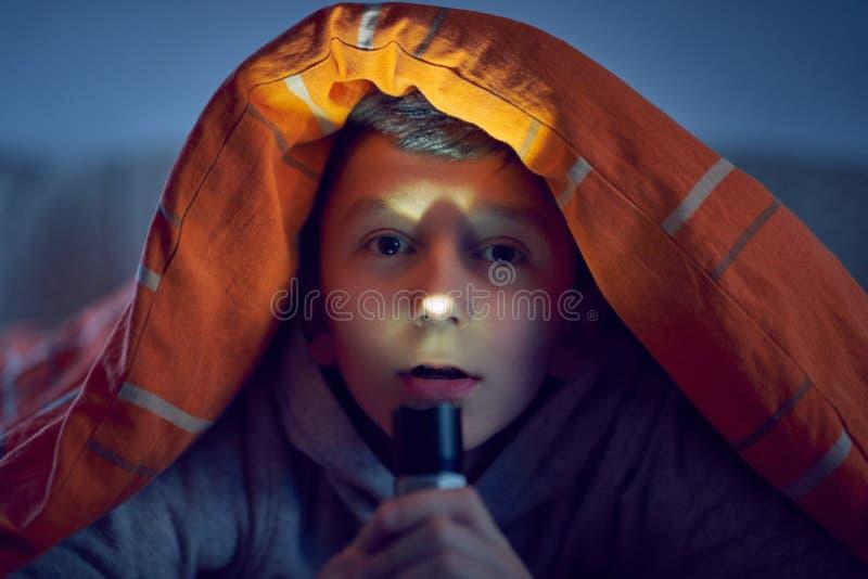 Un muchacho asustado con una luz que miente debajo de una manta imagen de archivo libre de regalías