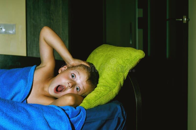 Un muchacho asustado en cama en la noche Miedos del ` s de los niños foto de archivo