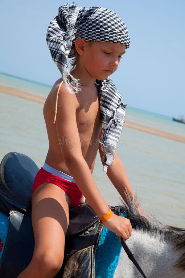 Un muchacho a caballo imagen de archivo libre de regalías