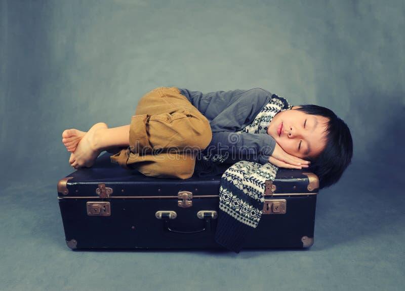 Un muchacho cansado que duerme en la maleta foto de archivo