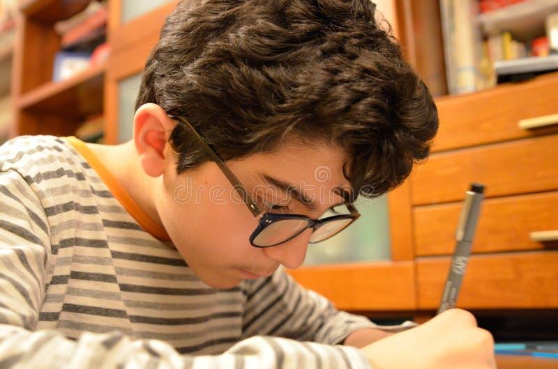 Un muchacho cauc?sico negro-cabelludo con los vidrios hace su preparaci?n de dibujo t?cnica imagen de archivo